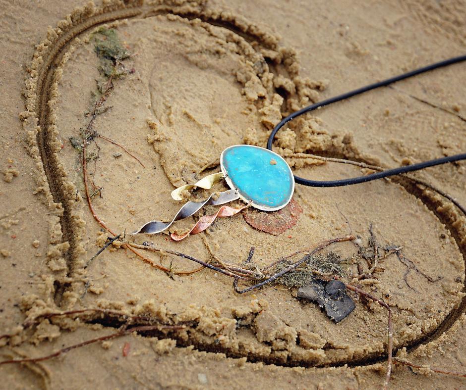 Wisior przypominający ośmiornicę w sercu narysowanym na piasku plaży.