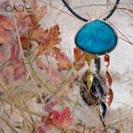 Błękitny wisior wśród jesiennych, kolorowych liści